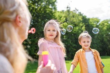 selective focus on mother blowing soap bubbles while spending time with kids in park