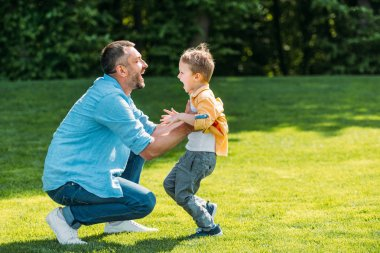 side view of cheerful father and son hugging and smiling each other in park