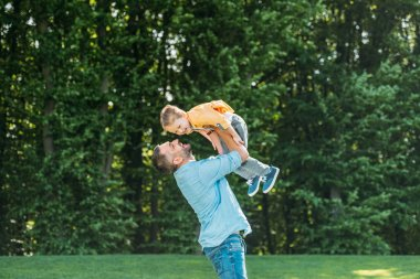 happy father carrying adorable smiling little son in park