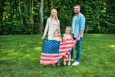 happy family with two children holding us flag and smiling at camera in park