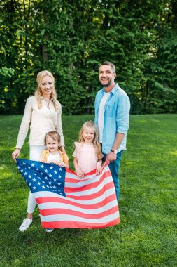 happy family with two kids holding american flag and smiling at camera in park