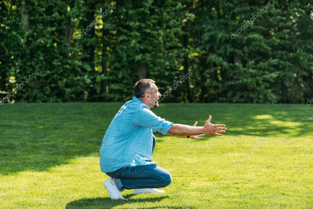 side view of happy man with open arms crouching and looking away in park