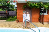 little siblings hugging each other near swimming pool on summer day