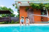 malý sourozenci sedět u bazénu v letním dni