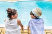 Rückansicht von kleinen Geschwistern, die an einem Sommertag in der Nähe des Schwimmbades sitzen