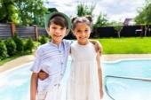 Fotografie Porträt von lächelnden kleinen Geschwister umarmen einander mit Swimmingpool hinter an Sommertag