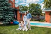 vidám családi labrador kutya látszó-on fényképezőgép, míg kiadási időt a Tájház udvarán nyári napon