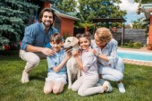 happy family with labrador dog looking at camera while spending time on backyard of country house on summer day