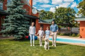 Fotografie glückliche Familie mit Labrador Hund Blick in die Kamera während Sie Hand in Hand im Garten des Landhauses auf Sommertag