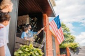 Fényképek family with american flag standing on country house porch
