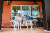 Fényképek smiling family sitting on sofa together on country house porch