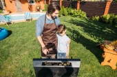 son looking at father cooking sausages and corn on grill on backyard