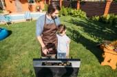 Fényképek nézte fiát apja, főzés kolbász és a háztáji grill kukorica