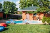 Fényképek vidéki ház a zöld gyep, a medence és a strand székek udvarban