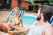 Fényképek a strand székek, miközben időt közelében úszómedence a kertben nyári napon kézen pár