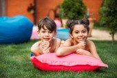 Fotografia portrait of cute kids resting on inflatable mattress on green lawn on backyard of country house