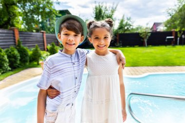 portrait of smiling little siblings hugging each other with swimming pool behind on summer day