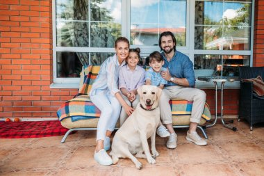 smiling family labrador dog sitting on sofa together on country house porch