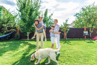 cheerful family with labrador dog spending time together on backyard on summer day