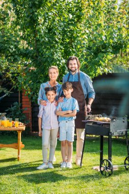 Happy family looking at camera while having barbecue together on backyard on summer day stock vector