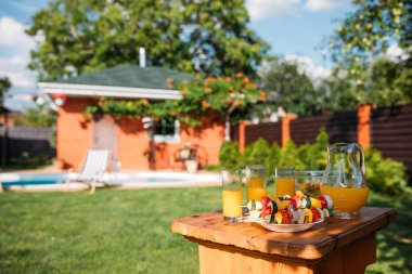 selective focus of fresh vegetables for barbecue and glasses of juice on backyard