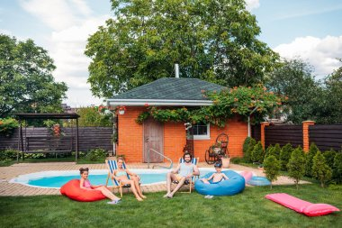 family resting on beach chairs and bean chairs near swimming pool at countryside backyard on summer day