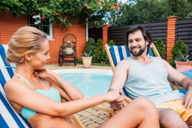 couple on beach chairs holding hands while spending time near swimming pool on backyard on summer day