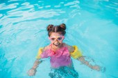 portrait of smiling kid in mask with water wing swimming in swimming pool on summer day