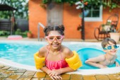 portrait of little siblings swimming in swimming pool together on summer day