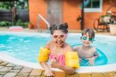 Kleine Geschwister schwimmen an Sommertagen gemeinsam im Schwimmbad