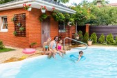 Fotografie happy family spending time near swimming pool at countryside backyard on summer day