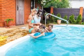 Familie verbringt an Sommertagen Zeit in der Nähe von Schwimmbad im Hinterhof