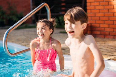 emotional little siblings swimming in swimming pool together on summer day