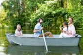 boční pohled na usmívající se mladé rodinné jízdy lodí na řeky v parku a při pohledu na fotoaparát