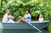 Fotografie side view of young family riding boat on river at park