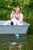 happy mother with son riding boat on lake at park and clapping hands