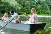 Fotografie beautiful young family riding boat on lake, using tablet and playing with toy plane