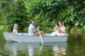 boční pohled s úsměvem mladá rodina trávit čas spolu v lodi na jezeře v parku