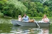 krásná mladá rodina trávit čas spolu v lodi na jezeře v parku
