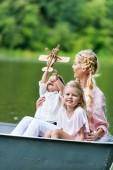 glückliche Mutter und Kinder beim Bootfahren auf dem See im Park