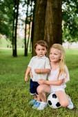 roztomilý malý bratr a sestra s fotbalový míč objetím v parku