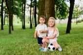 Photo little brother and sister with football ball embracing in park