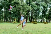 Fotografie side view of handsome father and daughter running with kite at park