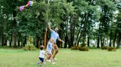 Fotografie side view of handsome father and kids playing with kite at park