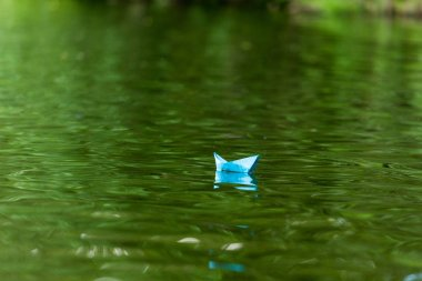 close-up shot of blue paper origami boat floating on water surface