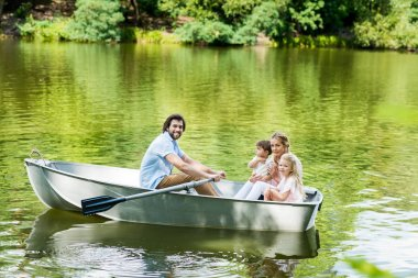 smiling young family riding boat on lake at park