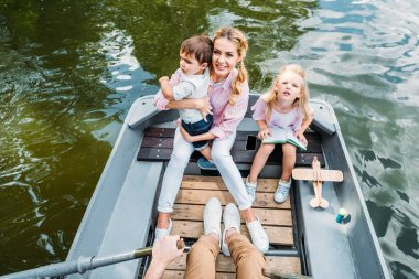 high angle view of beautiful young family riding boat on lake
