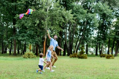 Side view of happy father and kids playing with kite at park stock vector