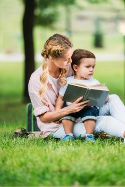 mother and son sitting with book on grass at park