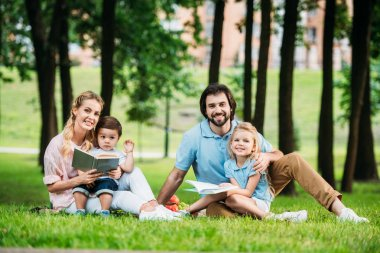 happy young family sitting on grass at park with books and looking at camera